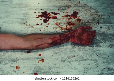 Hand in blood on a white vintage dirty floor in a pool of blood. Cut the veins on the hand. Homicide with a knife.