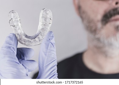 Hand with blue glove holding a dental splint, facing an adult man in front of white background