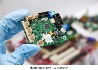 Hand in a blue glove holds pcb chip assembly on pcb backround on the production of printed circuit boards