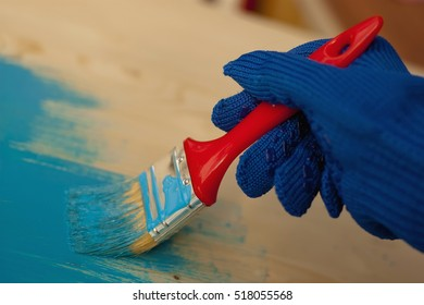 Hand in blue gloves painting wooden furniture, red brush, close up