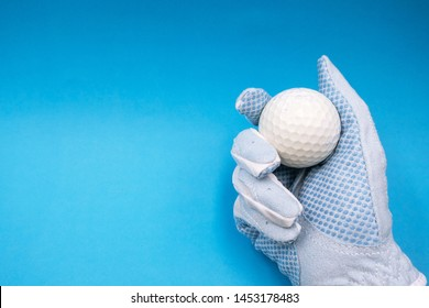 Hand in blue golf glove is holding white golf ball on blue sky background.