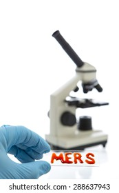 Hand in blue latex glove holds sample glass plate with blood inscripted MERS (aka novel coronavirus 2012 or Camel Flu) on it and microscope on white background