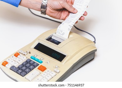hand in a blue shirt supports a paper check in the cash register on a white background