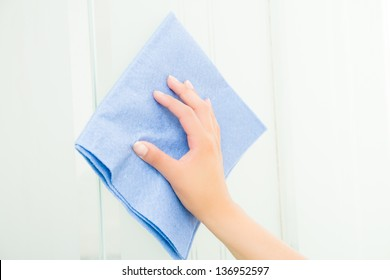 Hand with blue sponge cleaning the bathroom glass