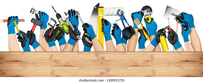 hand with blue working gloves and various diy handyman tools behind wooden planks with copy space isolated on white background