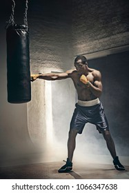 Hand of boxer and punching bag over black background. Strength, attack and motion concept. Fit african american model in movement. Afro muscular athlete in sport uniform. Sporty man during boxing
