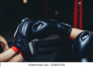 Hand in Boxing paw fight gear reflects kick of sports kickboxing glove on dark blurred background