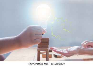 Hand of boy and girl holding lamp and effect abstract light and spark.In concept power and energy.