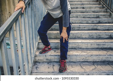 Hand of the boy holding the knee because of injury pain in leg, can not walk up the stairs.