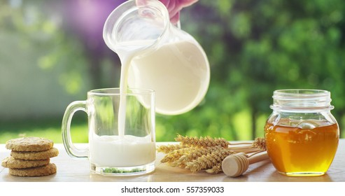 the hand of a boy on a sunny day in the garden pours milk in a transparent cup where milk falls in slow motion . concept of healthy food and breakfast of milk and biscuits or cookies