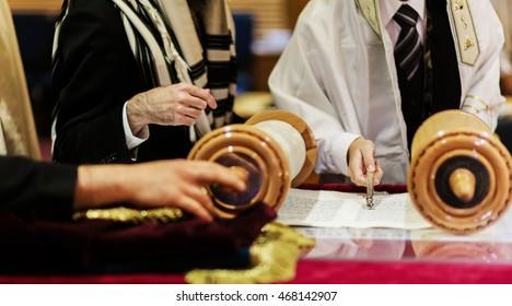 Hand of boy reading the Jewish Torah at Bar Mitzvah reading Jewish books