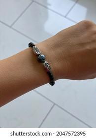 Main avec des bracelets avec des pierres gemmes noires vulcaines