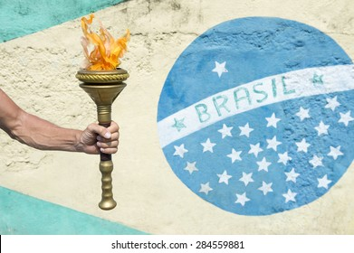 Hand of Brazilian athlete holding sport torch in front of a Brasil flag mural Rio de Janeiro Brazil