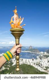 Hand of Brazilian torchbearer athlete holding sport torch against the city skyline with Sugarloaf Mountain in Rio de Janeiro, Brazil
