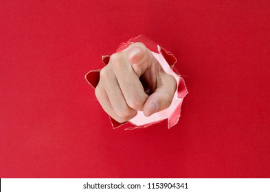 Hand breaking through red paper pointing at you.