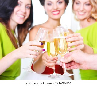 Hand of the bride, groom and bridal friends holding wedding glass with champagne