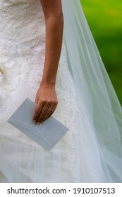 Hand of the bride holding an white enveloppe from a guest and wedding ring at her hand. Her white weddingdress is background.