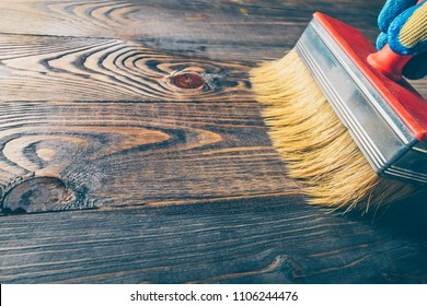 Hand brush covers with oil old wooden floor - repair and restoration of the floor