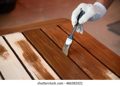 Hand with a brush paints a wooden surface with brown paint, close up.