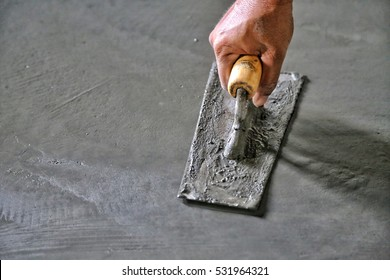 hand of builder worker plastering at wall