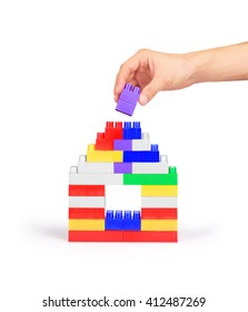 Hand building a house of blocks on a white background
