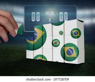 Hand building wall against football pitch with black scoreboard