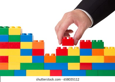 hand building up a wall by stacking up block