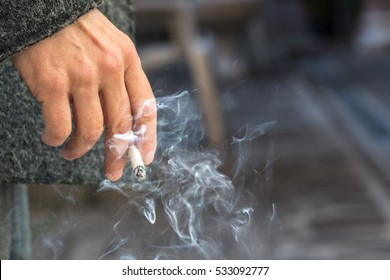 Hand with burning cigarette