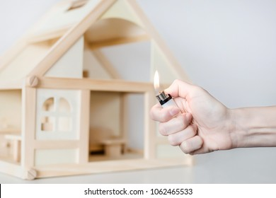 Hand with burning lighter against wooden house model on the background. Arson of house concept. Criminal accident