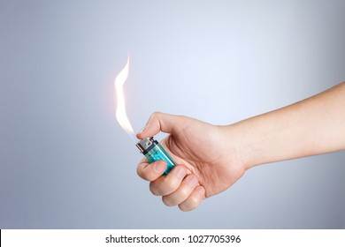 Hand burning a lighter on white background
