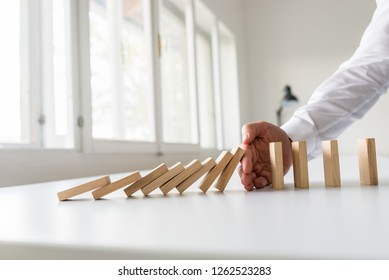 Hand of a business advisor stooping domino effect by intervening at the right moment.