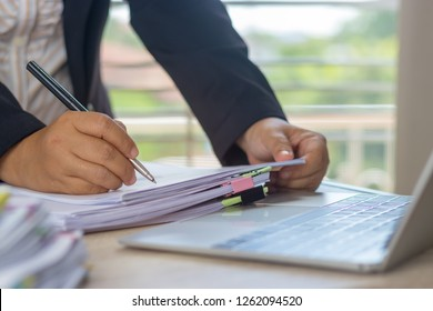 Hand of business analyst holding pen is analyzing graphs about marketing in office. Unfinished paperwork stacked in archive with color binder paper clips. Business and Education concept.