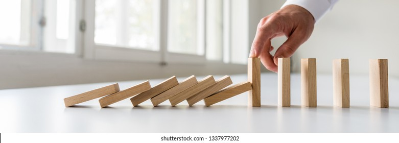 Hand of a business crisis manager stopping falling dominos to prevent a total collapse and establish stability.