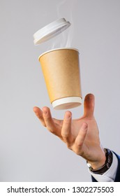 Hand of a business man in a blue jacket, white shirt and watch catches a flying cup of hot coffee with steam from a drink. Coffee break advertising concept. Empty place for your logo placement.