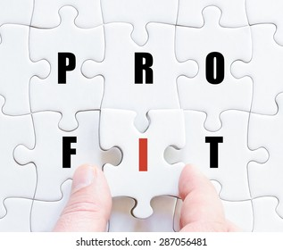 Hand of a business man completing the puzzle with the last missing piece.Concept image of puzzle board with motivational word PROFIT
