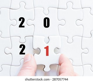 Hand of a business man completing the puzzle with the last missing piece. Concept image of puzzle board with year 2021