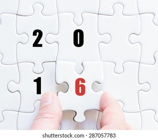 Hand of a business man completing the puzzle with the last missing piece. Concept image of puzzle board with year 2016