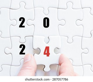 Hand of a business man completing the puzzle with the last missing piece. Concept image of puzzle board with year 2024