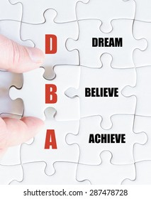 Hand of a business man completing the puzzle with the last missing piece.Concept image of Business Acronym DBA as Dream Believe Achieve