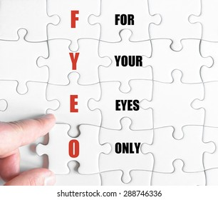Hand of a business man completing the puzzle with the last missing piece.Concept image of Business Acronym FYEO as For Your Eyes Only