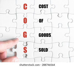 Hand of a business man completing the puzzle with the last missing piece.Concept image of Business Acronym COGS as Cost Of Goods Sold