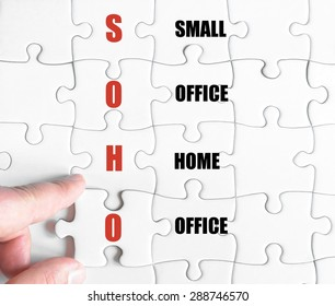 Hand of a business man completing the puzzle with the last missing piece.Concept image of Business Acronym SOHO as Small Office Home Office