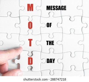 Hand of a business man completing the puzzle with the last missing piece.Concept image of Business Acronym MOTD as Message Of The Day