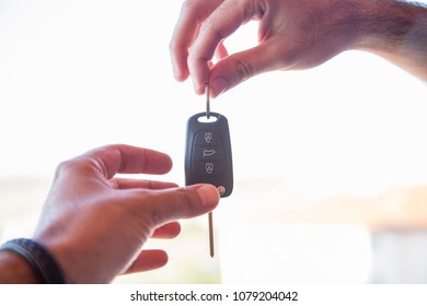 Hand of business man gives the car key with isolated on white