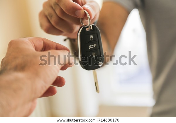 Hand of business man gives the car key