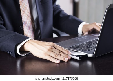 Hand of Business man holding Disk insert to laptop computer