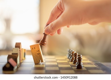 Hand of business man moving chess to Building and house models in chess game, competition success play. strategy, management or leadership concept