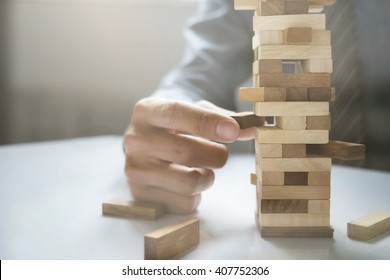 Hand of business man planning, risk and strategy in business.Businessman gambling placing wooden block on a tower.