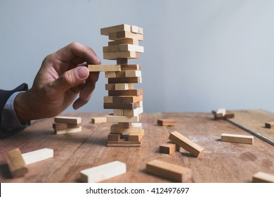 Hand of business man planning, risk and strategy in business.Businessman gambling placing wooden block on a tower with copy space.