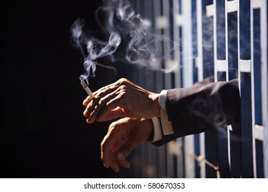 hand of business man smoking in jail with copyspace background.